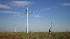 Een jonge mens op een fiets berijdt voorbij een windenergieinstallatie stock footage