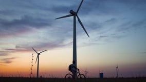 Een jonge mens op een fiets berijdt voorbij een windenergieinstallatie bij zonsondergang stock video