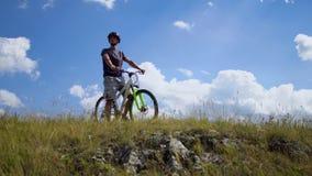Een jonge mens op een fiets houdt op de rotsachtige rand van de heuvel op en kijkt rond stock videobeelden