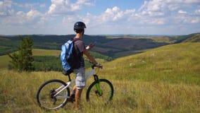 Een jonge mens op een fiets wordt begeleid door het terrein gebruikend een kaart op zijn mobiele telefoon stock videobeelden
