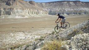 Een jonge mens op een fiets rolt van de berg Langzame Motie Royalty-vrije Stock Foto