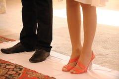 Een jonge mens in reusachtige schoenen en een meisje in rode schoenen Royalty-vrije Stock Fotografie