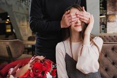 Een jonge mens sluit zijn ogen aan het meisje, zijn vrouw, en geeft een boeket van rode bloemen in een koffie door het venster stock afbeeldingen