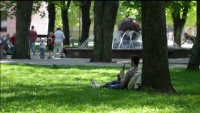 Een jonge mens speelt de saxofoonzitting onder boom in het park stock videobeelden