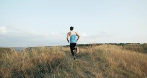 Een jonge mens in een sportenkostuum dat oefeningen op een kabel voor duurzaamheid gekneed in de aard op berg, de atleet doet stock videobeelden