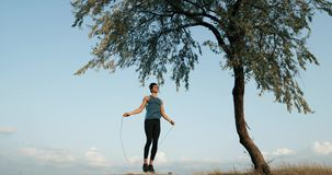 Een jonge mens in een sportenkostuum dat oefeningen op een kabel voor duurzaamheid gekneed in de aard doet, de atleet springt tot stock videobeelden