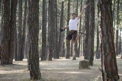 Een jonge mens springt door de bomen royalty-vrije stock afbeelding