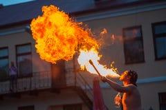 Een jonge mens spuit een brand uit zijn mouththe de jonge mens brand van zijn mond spuit schouwspel voor bezoekers royalty-vrije stock fotografie