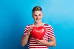 Een jonge mens in een studio, die rode hartballon voor hem houden stock afbeelding
