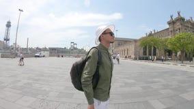 Een jonge mens, toerist status met een rugzak en in een hoed en neemt foto's door smartphone dichtbij Columbus Monument stock video