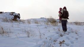 Een jonge mens vervoert een kind in zijn wapens op een snow-covered heuvel een blizzard begint met stock video