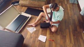 Een jonge mens verzamelt onafhankelijk meubilair in de woonkamer van zijn huis Een mens verzamelt een computerbureau stock foto