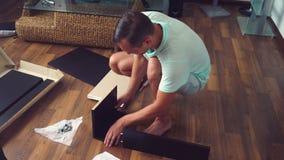 Een jonge mens verzamelt onafhankelijk meubilair in de woonkamer van zijn huis Een mens verzamelt een computerbureau royalty-vrije stock afbeeldingen