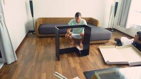 Een jonge mens verzamelt onafhankelijk meubilair in de woonkamer van zijn huis Een mens verzamelt een computerbureau royalty-vrije stock foto