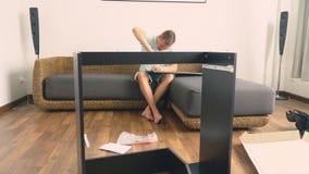 Een jonge mens verzamelt onafhankelijk meubilair in de woonkamer van zijn huis Een mens verzamelt een computerbureau stock afbeelding