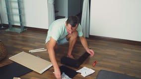 Een jonge mens verzamelt onafhankelijk meubilair in de woonkamer van zijn huis Een mens verzamelt een computerbureau stock fotografie