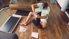 Een jonge mens verzamelt onafhankelijk meubilair in de woonkamer van zijn huis Een mens verzamelt een computerbureau stock foto's