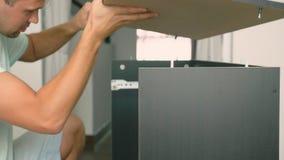 Een jonge mens verzamelt onafhankelijk meubilair in de woonkamer van zijn huis Een mens verzamelt een computerbureau stock afbeeldingen