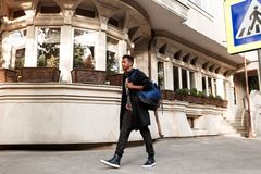 Een jonge mens in vrijetijdskleding, met rugzak op schouders, die op straat in dagtijd lopen, dichtbijgelegen gebouwen, zebrapad stock foto