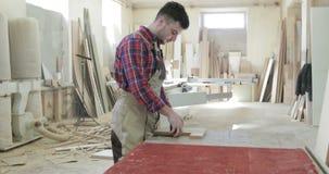 Een jonge mens werkt bij de meubilairproductie stock videobeelden