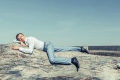 Een jonge mens in een wit overhemd en blauwe broeken ligt royalty-vrije stock foto's