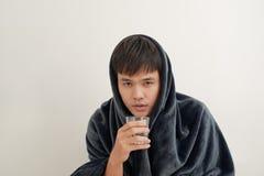 Een jonge mens is ziek met griep, ligt thuis onder een deken, neemt een pil stock foto
