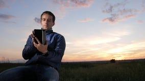 Een jonge mens zit bij zonsondergang en controleert de berichten om de berichten op de tablet te controleren Mooie hemel erachter stock footage