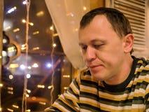 Een jonge mens zit in de avond in een koffie dichtbij het venster stock afbeelding