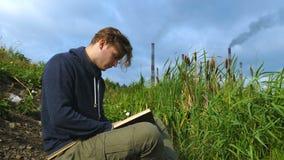 Een jonge mens zit door de rivier en leest een boek stock videobeelden