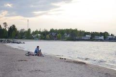 Een jonge mens zit naast een fiets op de zandige kust royalty-vrije stock afbeelding
