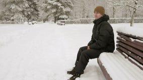 Een jonge mens zit op een bank in de winter park en het bewonderen van de sneeuw Een mens in een donker jasje en een warme hoed stock footage