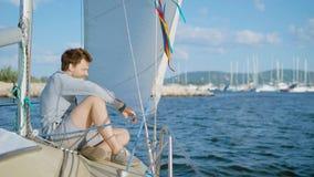 Een jonge mens zit op het dek van een jacht dat zich van de pijler en de zeilen aan het overzees of de oceaan, in de afstand heef stock video