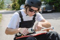 Een jonge mens in zonnebril en overall met een helm op zijn hoofd verandert zijn wielen op zijn longboard onder de open hemel stock afbeeldingen