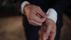 Een jonge mens in zwart kostuum past zijn cufflinks van wit overhemd aan stock video