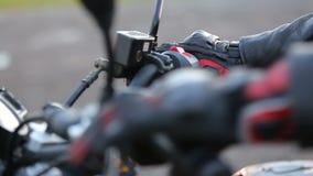 Een jonge mens in zwart leerjasje en beschermende handschoenen zit op motorfiets en bevoegdheden motor vóór reis bij de herfstzon stock video