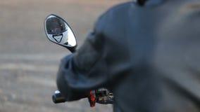 Een jonge mens in zwart leerjasje zit op motorfiets voorbereidt zijn witte helm vóór reis bij de herfstzonsondergang stock videobeelden