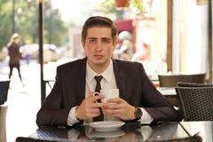 Een jonge mens in een zwart pak, een witte overhemd en een band zit in een koffie van de stadsstraat bij een lijst en geniet van  royalty-vrije stock fotografie