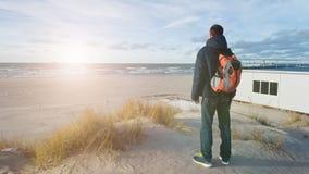 Een jonge mensenreiziger met een rugzak bevindt zich op het strand en bewondert de mening Het denken over de alleen toekomst Mooi royalty-vrije stock afbeelding