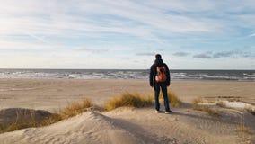 Een jonge mensenreiziger met een rugzak bevindt zich op het strand en bewondert de mening Het denken over de alleen toekomst Mooi royalty-vrije stock afbeeldingen