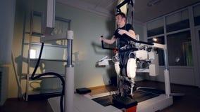 Een jonge mensentreinen binnen een groot medisch exoskeleton systeem stock footage
