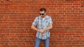 Een jonge modieuze Kaukasische mens met een baard danst en verheugt zich tegen een bakstenen muur, exemplaarruimte, langzaam-mo,  stock video