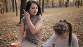 Een jonge moeder is bezig geweest met het opheffen van een dochter Het meisje trekt met krijt op een bord Familievakantie in stock footage