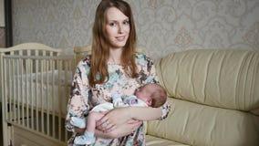 Een jonge moeder die een kind in haar wapens schommelen stock videobeelden