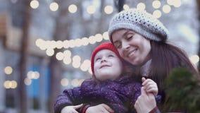 Een jonge moeder die met haar weinig dochter knuffelen die haar en op een bank zitten houden Een gelukkige familie Lichten op bac stock footage