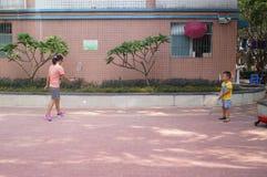 Een jonge moeder en een zoon spelen badminton Royalty-vrije Stock Afbeeldingen