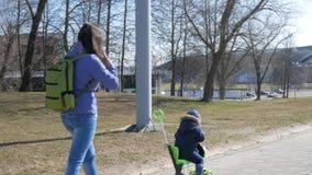 Een jonge moeder en een jongen lopen buiten Het jonge geitje schaatst zittend op de autoped stock footage