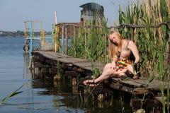 Een jonge moeder en een zoon rusten op de brug door de rivier Bevat gradiënt en het knippen masker stock afbeeldingen