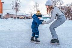 Een jonge moeder houdt de hand van een klein jongens 2-4 jaar oud kind In de winter, op piste in stad Het gelukkige ontspannen in stock afbeeldingen