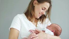 Een jonge moeder houdt haar slaap pasgeboren baby in haar wapens plaatsvervanging IVF Reageerbuisbaby stock videobeelden