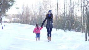 Een jonge moeder met een jonge dochter in het sneeuwbos stock video